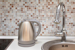 Silver kettle. Appliance on modern kitchen counter stock photo