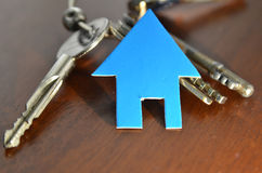 Silver key with blue house figure Royalty Free Stock Images