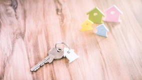 Silver Key with Breloque in Form of House on Vhain with some Miniature Symbol of Houses on Side in Different Colours on Royalty Free Stock Photography
