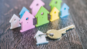 Silver Key with Breloque in front of Miniature Symbols of Houses in Different Colours on Dark Wooden Surface Royalty Free Stock Images