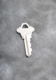 Silver key on gray background Royalty Free Stock Photography