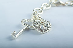 Silver Key and Heart Lock Bracelet. Silver Key and Heart Shaped Lock with diamonds attached to a bracelet Royalty Free Stock Photos