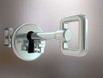 Silver key in keyhole Stock Images