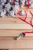 Silver key with red ribbon and trash paper.jpg Royalty Free Stock Images