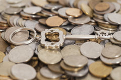 Silver Key on Stack of coins Royalty Free Stock Photo