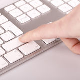 Silver keyboard with woman finger Royalty Free Stock Images
