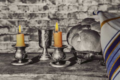 Silver kiddush cup, crystal candlesticks with lit candles, and challah. Challahs Stock Photography