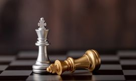 silver king standing and gold falling on chess board stock image