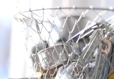 Silver kitchen storage basket. A hanging silver mesh basket for kitchen utensil storage stock image