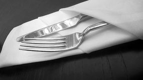 Silver knife and fork in linen serviette Royalty Free Stock Photos