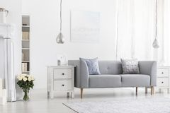 Silver lamps above white cabinets in apartment interior with flowers and grey settee. Real photo stock photos