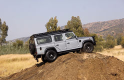 Silver Land Rover Defender 110 SW on 4x4 Course Royalty Free Stock Photos