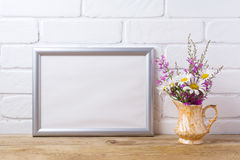 Silver landscape frame mockup with chamomile and purple flowers royalty free stock image