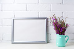 Silver landscape frame mockup with maroon purple flowers in mint. Silver landscape frame mockup with maroon purple field flowers in polka dot mint green pitcher Royalty Free Stock Images