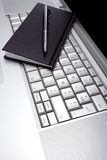 Silver lap top and black pocket planner Royalty Free Stock Image