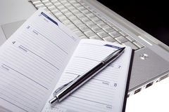 Silver lap top and opened pocket planner close up Stock Photo