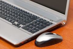 Silver laptop. With mouse in the office Stock Photo
