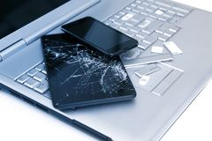 A silver laptop with a broken keyboard, tablet with a cracked display and black phone. A close-up picture of part of broken laptop. And cracked screen on a stock images
