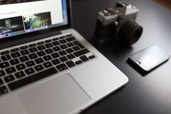 Silver Laptop Computer Beside of White and Black Camera and Black Iphone Stock Photo