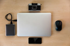Silver laptop with media equipment. Laptop with external harddrive, camera, mouse and smart phone on wood. View from above Royalty Free Stock Images