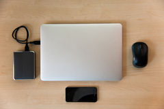 Silver laptop with media equipment. Laptop with external harddrive, mouse and smart phone on wood. View from above Stock Photo