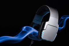 Silver large headphones with stream of blue smoke. Single object on black background Stock Images
