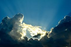 Silver Lining. Stunning view of sunlight escaping through the clouds, just before sunset, producing a silver lining Royalty Free Stock Images