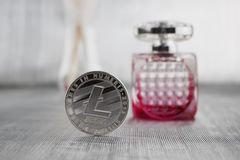 SIlver litecoin coin and fragrance. Digital currency silver litecoin coin near pink fragrance in luxury bottle Stock Photos