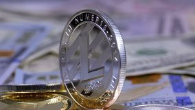 Silver Litecoin Coin, LTC and Bills of Dollars are Rotating. Different Crypto Currency Close-up. Macro. Dollar banknotes of various denominations on which lies stock video
