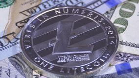 Silver Litecoin Coin, LTC and Bills of Dollars are Rotating. Crypto Currency Close-up. Macro. Dollar banknotes of various denominations on which lies the stock footage