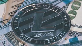 Silver Litecoin Coin, LTC and Bills of Dollars are Rotating. Crypto Currency Close-up. Macro. Dollar banknotes of various denominations on which lies the stock video
