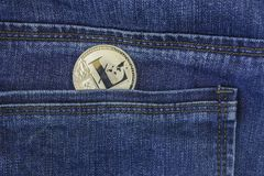Silver litecoin lie back pocket of blue jeans closeup. Silver litecoin crypto-currency llie back pocket of blue jeans closeup stock photography