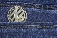 Silver litecoin lie back pocket of blue jeans closeup. Silver litecoin crypto-currency llie back pocket of blue jeans closeup royalty free stock photo