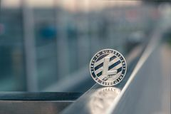Silver Litecoin stand on metal handrail. Outdoor stock photo