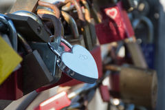 Silver lock in heart shape on a bridge Stock Photos
