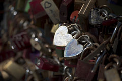 Silver love locks in heart shape on a bridge railing Royalty Free Stock Image