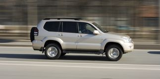 Silver luxury suv car. A silver luxury japanese car, driving fast Royalty Free Stock Photos