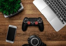 Silver Macbook Beside Black Sony Ps4 Dualshock 4, Silver Iphone 6, and Round Black Keychain on Brown Wooden Table Royalty Free Stock Images