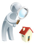 Silver man looking at house. Person looking at a a house with a magnifying glass, could be searching for a house to buy or doing a home survey Stock Photo