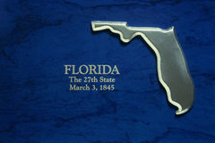 Silver map of state of Florida. This is a silver map of the state of Florida. It is against a blue background. It reads, Florida, the 27th State, March 3, 1845 stock image
