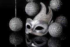 Silver Mask with Holiday Ornaments. A silver female mask surrounded by silver holiday ornaments on black reflective surface. A concept for holiday and masquerade stock images