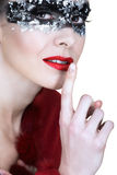 Silver mask and red lips. Beautiful woman in silver leaf and black mask, holding finger next to her red lips stock photography