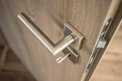 Silver matte door handle on an oak wooden door Royalty Free Stock Image