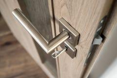 Silver matte door handle on an oak wooden door Stock Photography