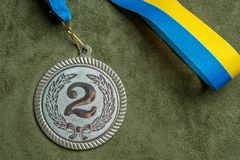 Silver medal with a yellow and blue ribbon. Close-up royalty free stock photography
