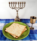 Silver Menorah and plate of Matsah. Passover plate with matzah under a silver menorah next to a gold goblet of wine Stock Photos