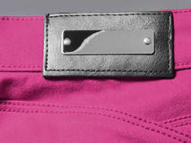 Silver metal and black leather empty label on pink denim Royalty Free Stock Photo
