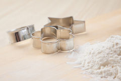 Silver metal cookie mold on wooden table with flour Royalty Free Stock Image