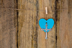 Silver metal crucifix hanging with a blue heart on string agains. T old rustic wooden background stock image