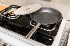 Silver metal frying pan covered with oil splatter screen. On gas stove Royalty Free Stock Image